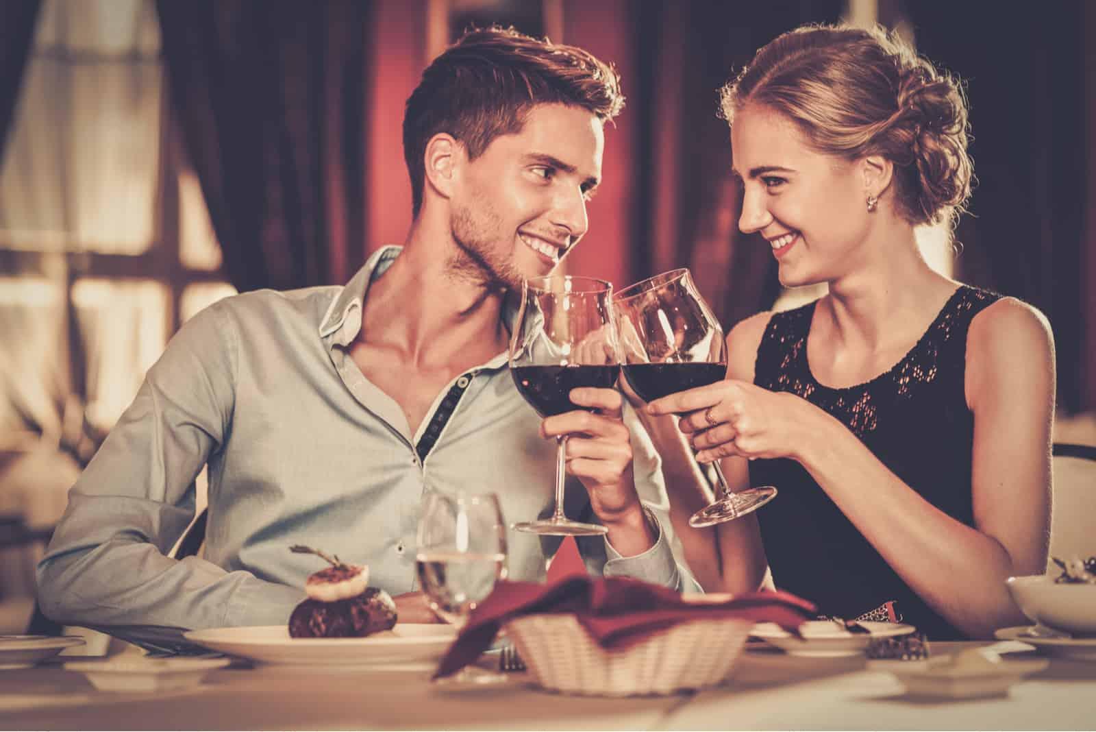 Schönes junges Paar mit Gläsern Rotwein im Luxusrestaurant