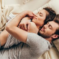Schönes glückliches junges Paar, das sich beim Schlafen auf dem Bett umarmt
