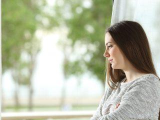 Frau, die zu Hause durch ein Fenster nach draußen schaut