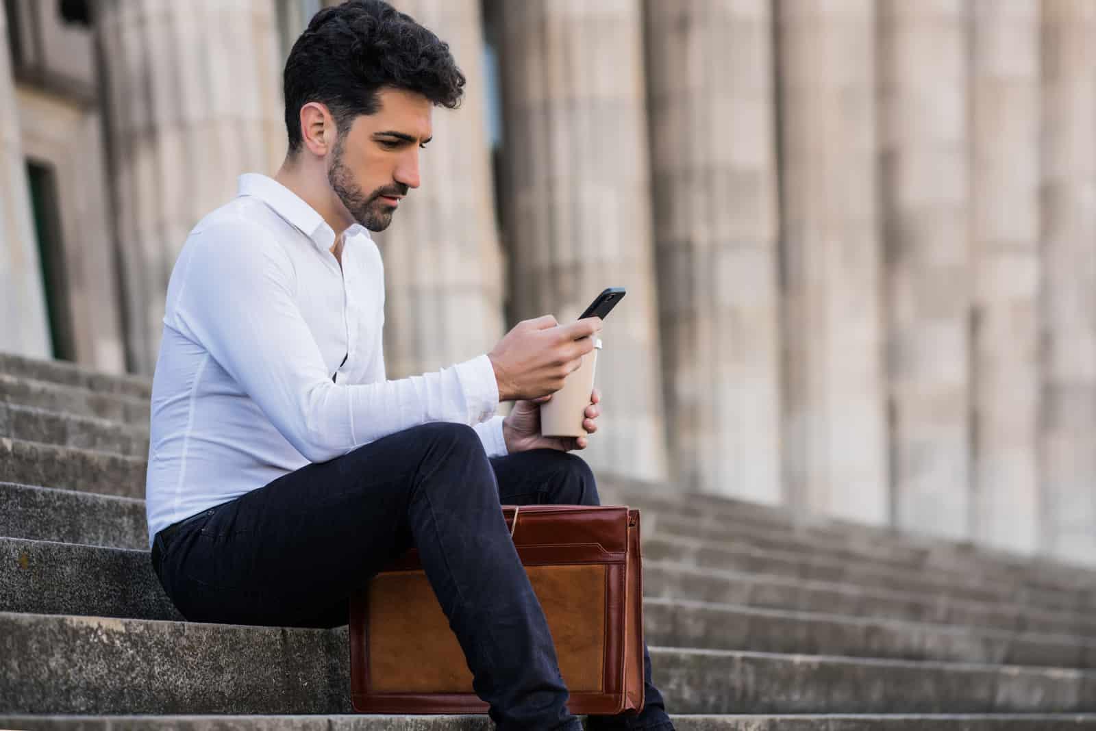 ein Mann sitzt auf der Treppe und ein Knopf am Telefon