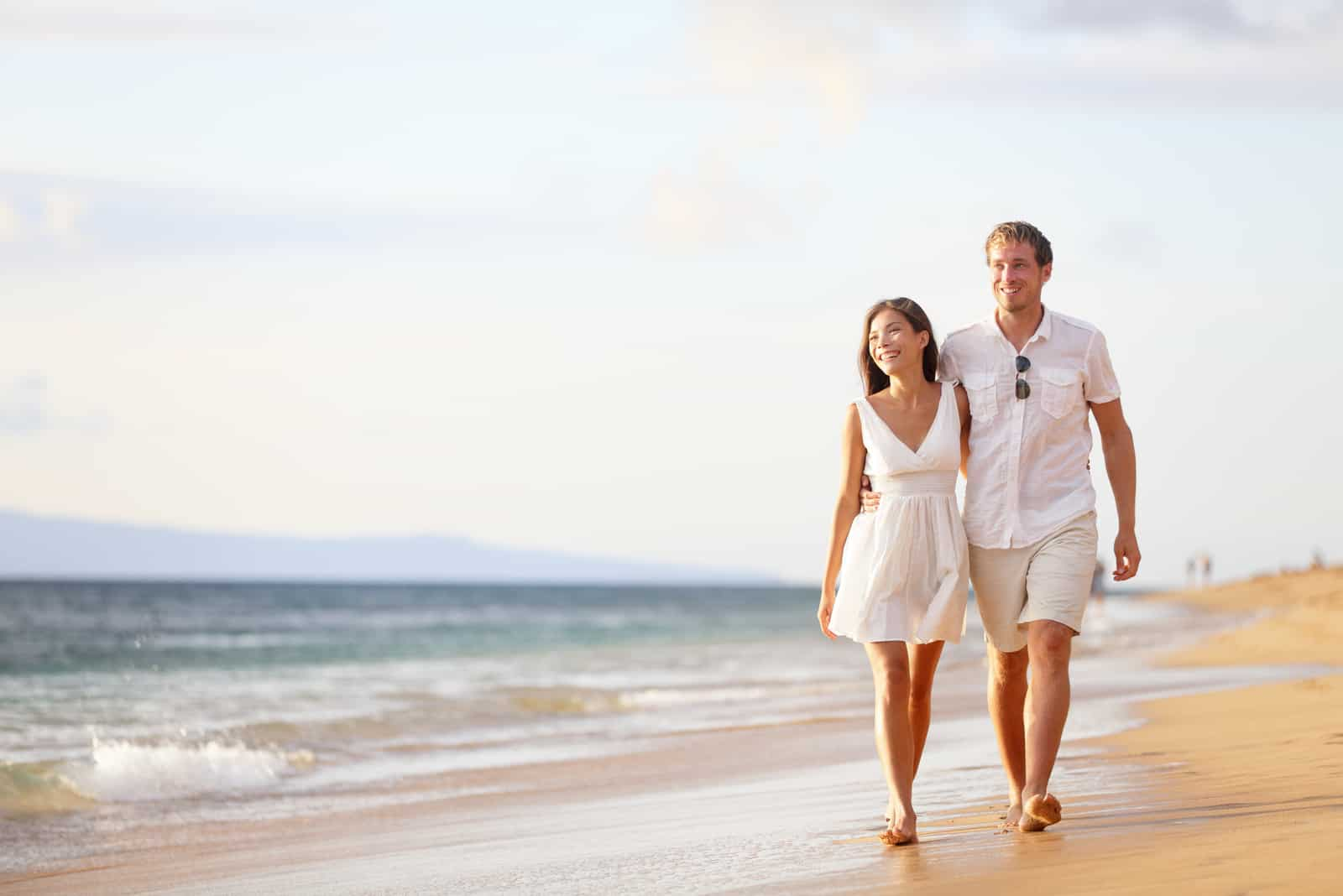 ein Mann und eine Frau gehen am Strand entlang