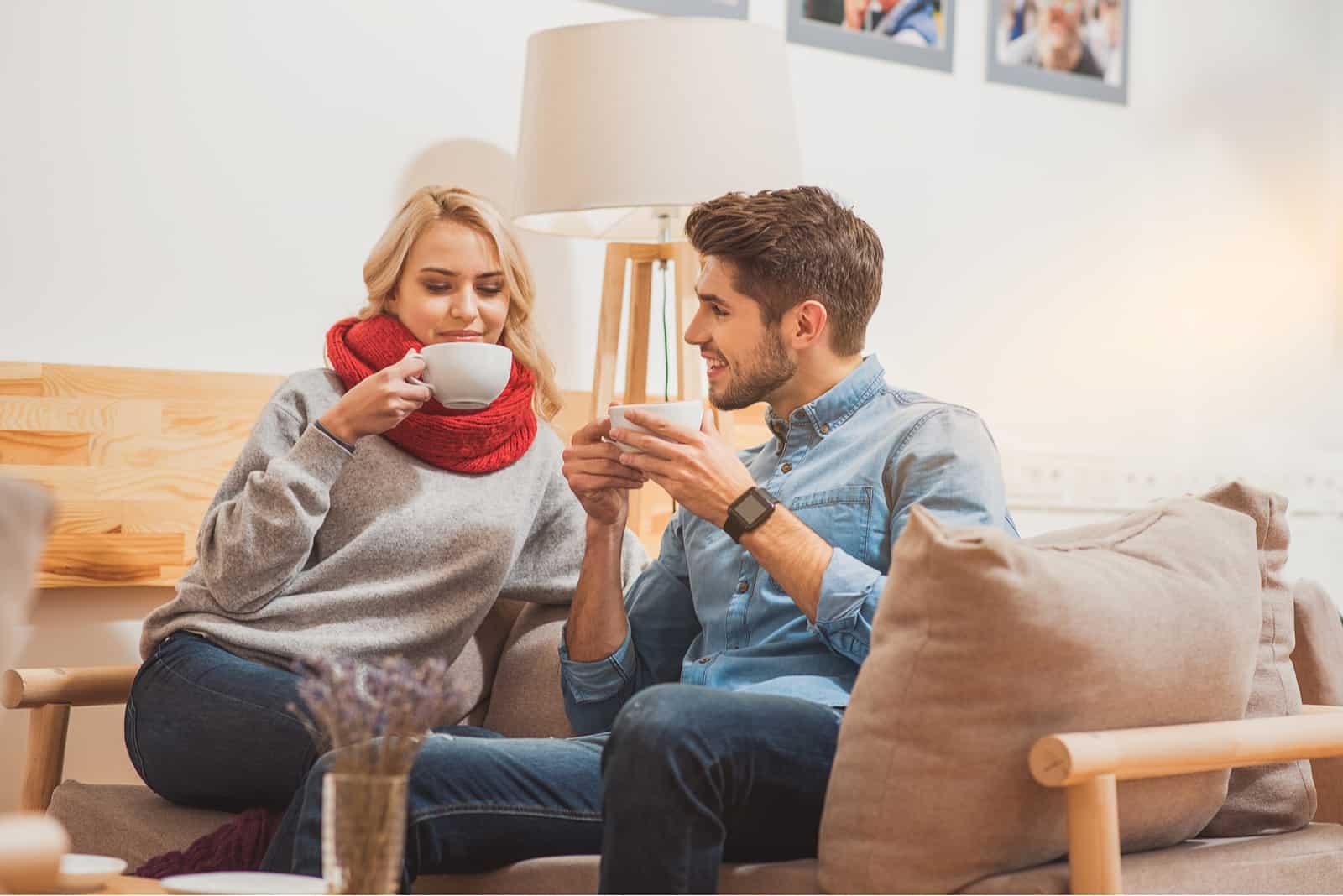 ein Mann und eine Frau sitzen auf einem Abschnitt und trinken Kaffee