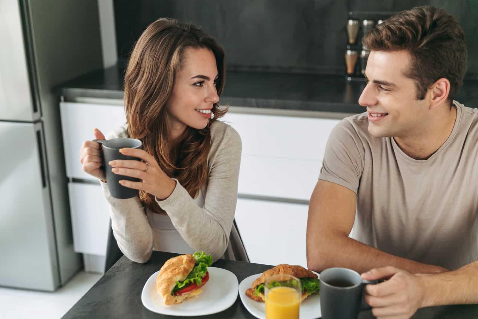ein Mann und eine Frau sitzen beim Frühstück an einem Tisch und unterhalten sich