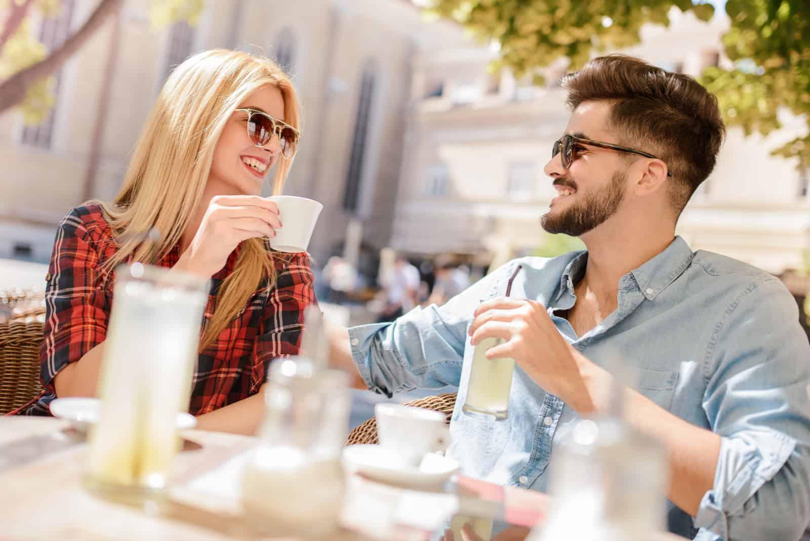 ein Mann und eine Frau sitzen draußen, trinken Kaffee und unterhalten sich