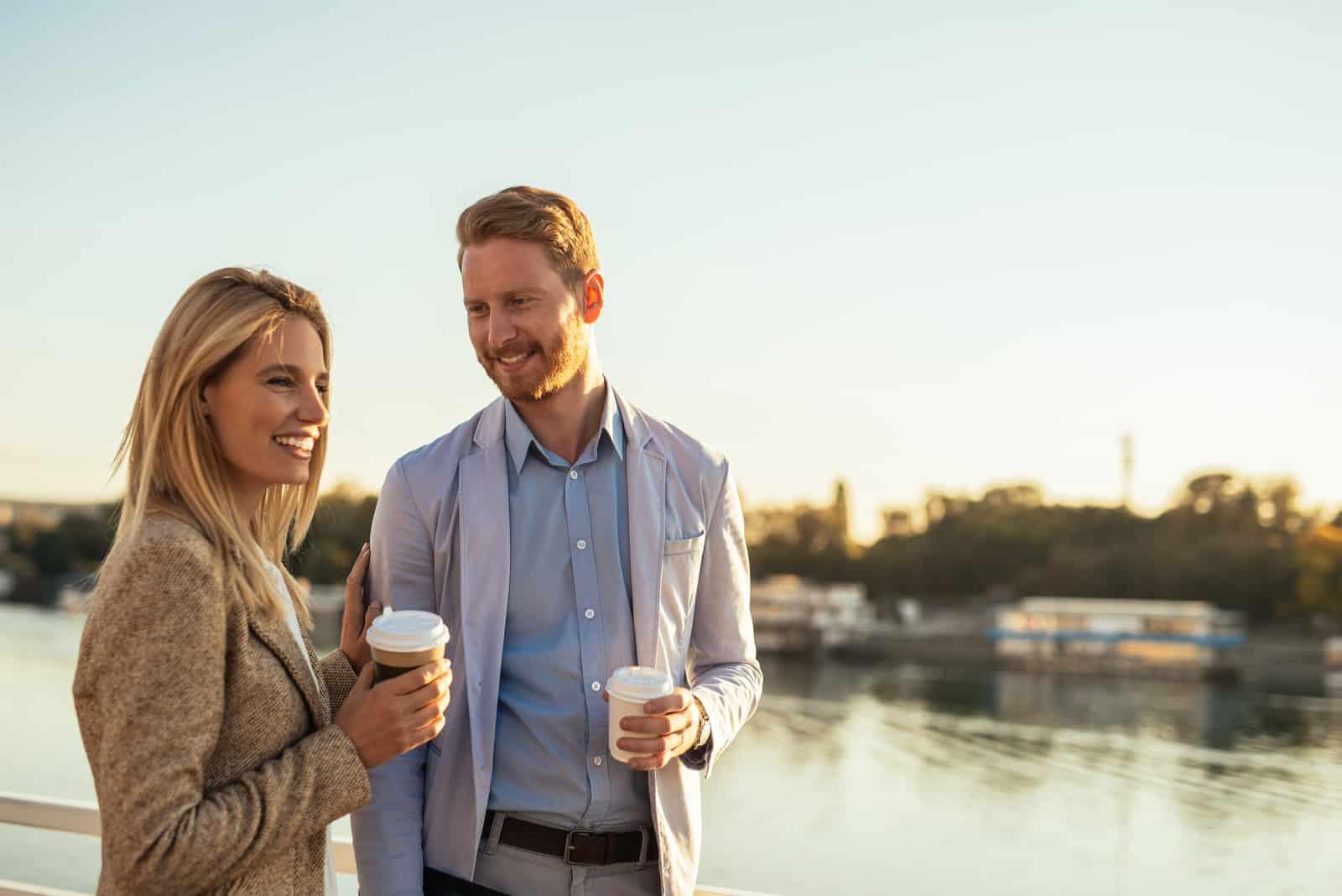 ein Mann und eine Frau stehen mit Kaffee in den Händen und unterhalten sich