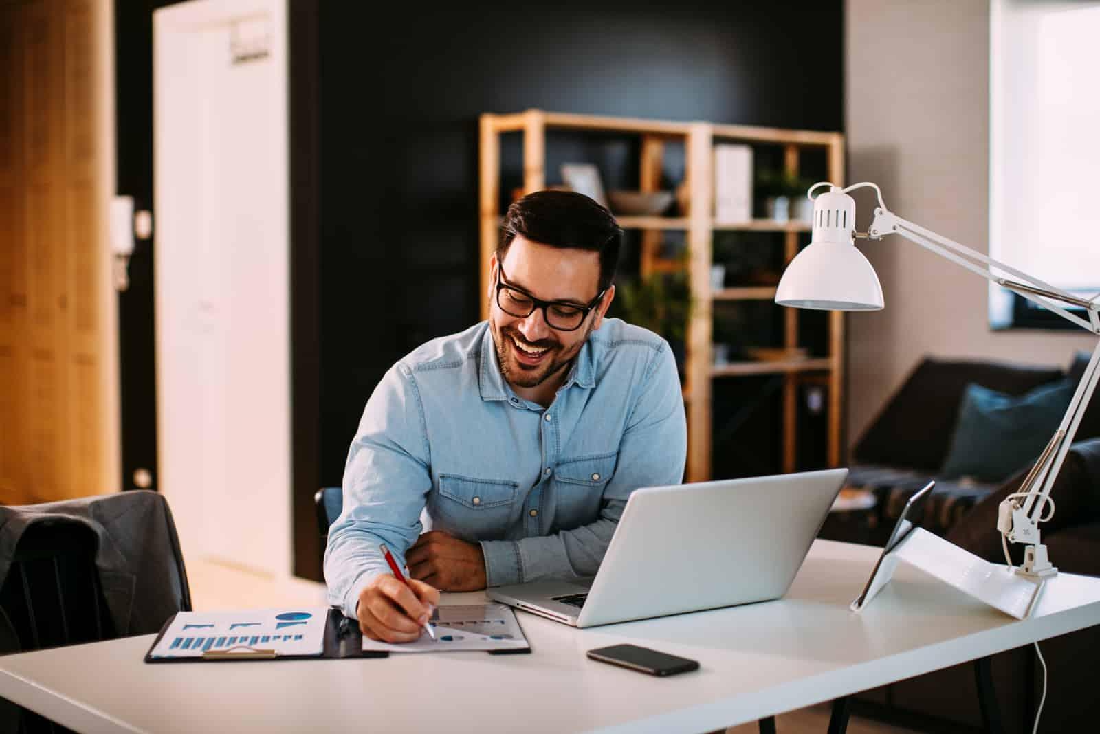 ein lächelnder mann sitzt an seinem laptop und arbeitet