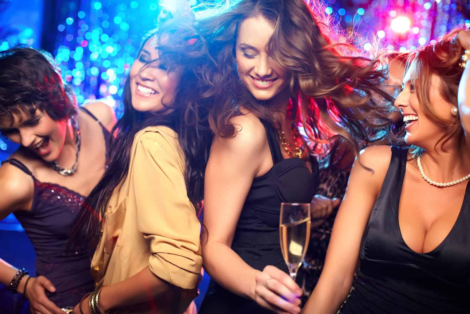 eine Frau in einem schwarzen Kleid tanzt mit Freunden