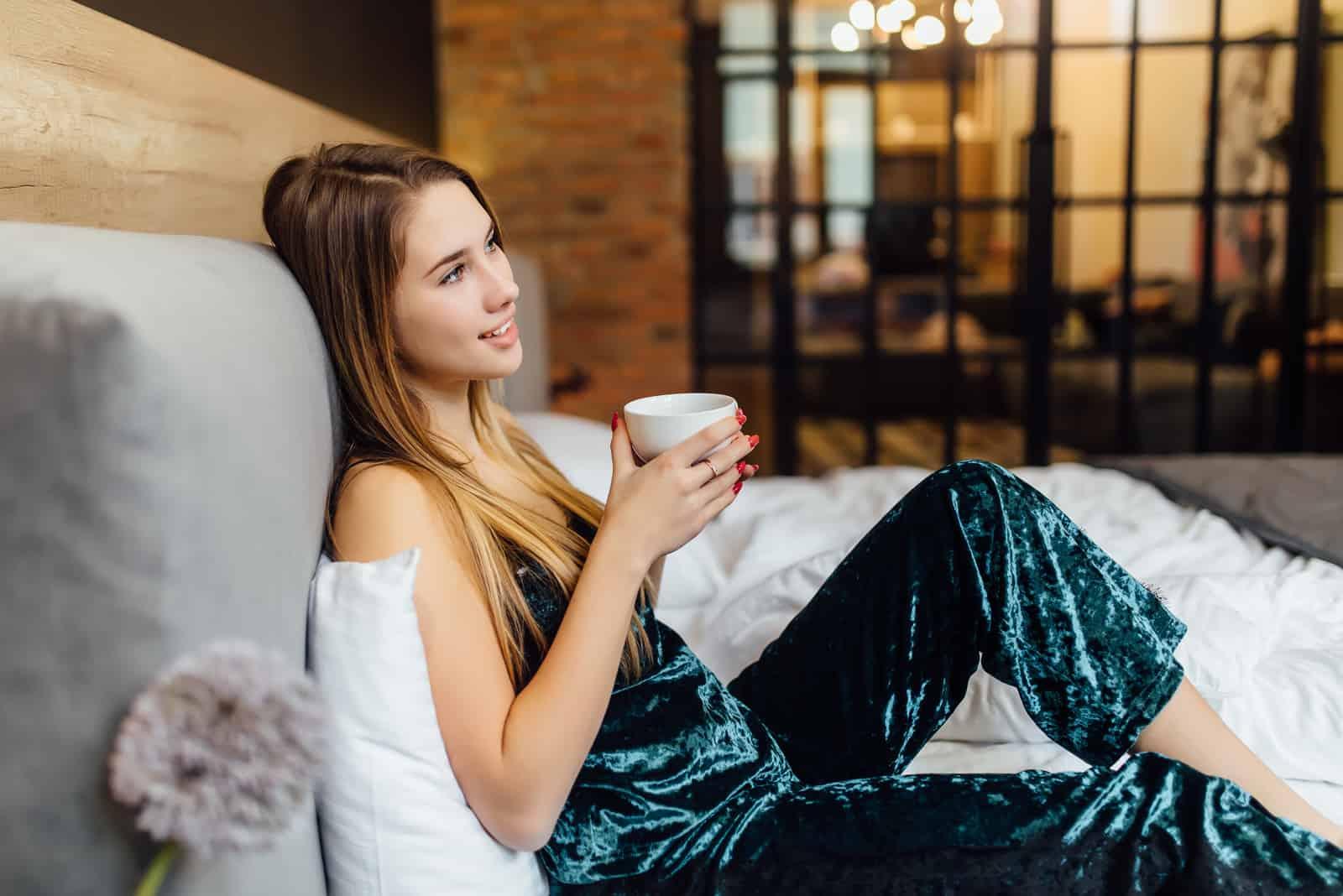 eine lächelnde frau liegt im bett und trinkt kaffee