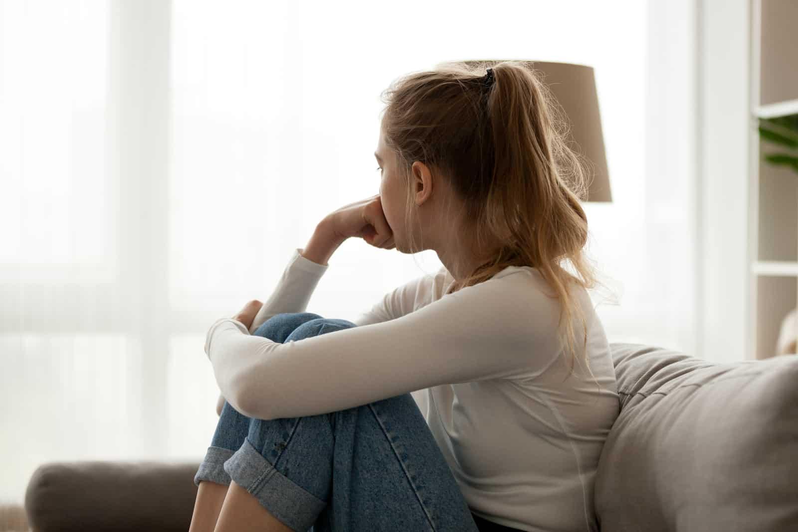 junge Frau, die zu Hause auf der Couch sitzt und am Fenster wegschaut