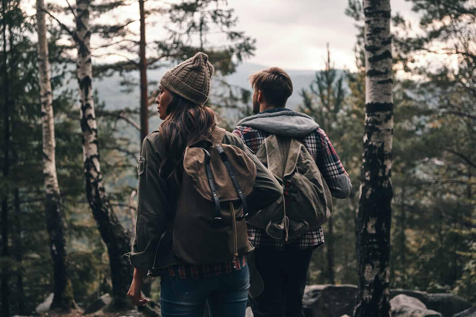 junges Paar, das beim gemeinsamen Wandern im Wald steht und wegschaut