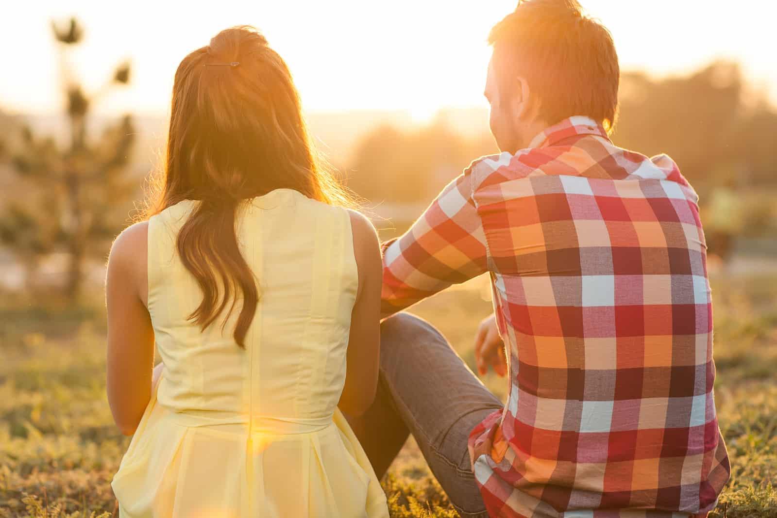 junges glückliches Paar, das bei Sonnenuntergang auf dem Gras sitzt
