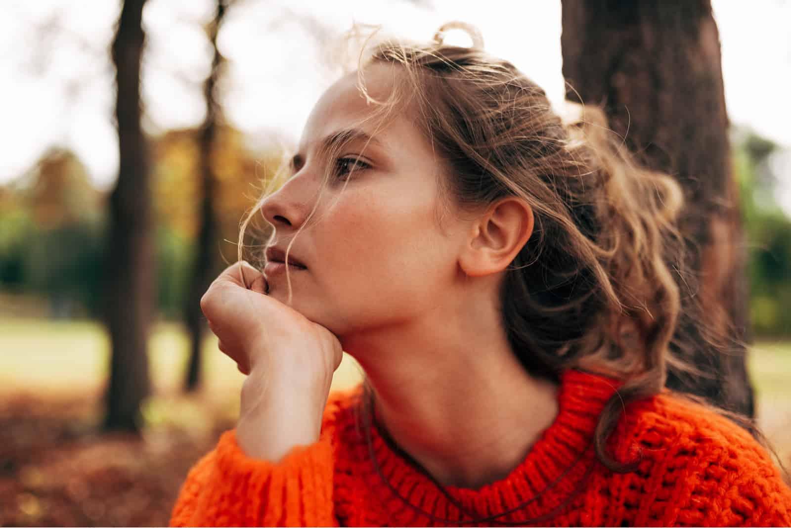 nachdenkliche Frau mit orangefarbenem Strickpullover