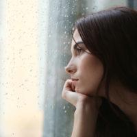 Depressive junge Frau am Fenster zu Hause