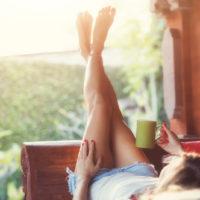 Mädchen trinkt Kaffee und genießt den Sonnenaufgang im Garten