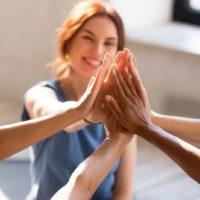 Fröhliche, vielfältige junge Mädchen, die zusammen im Sportstudio sitzen, bevor sie mit dem Training beginnen, fühlen sich glücklich und gesund, Nahaufnahme der Hände.