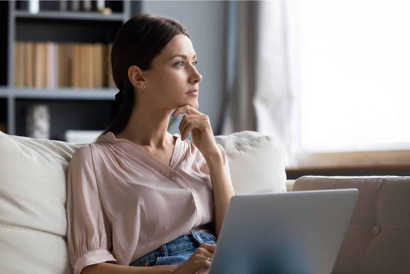 Abgelenkt von der Arbeit besorgte junge Frau, die mit Laptop auf der Couch sitzt und an Probleme denkt.