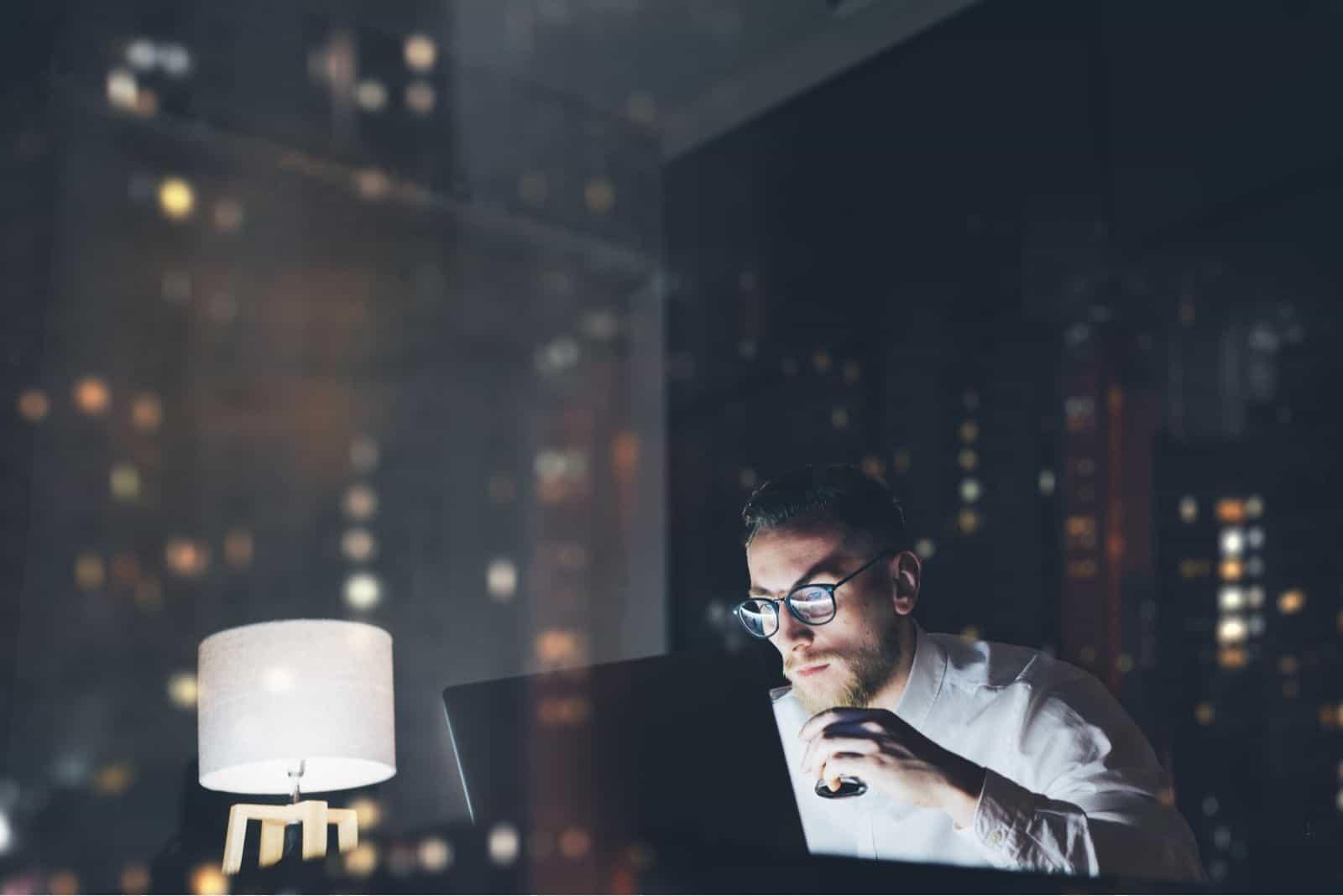 Bärtiger junger Geschäftsmann, der nachts an einem modernen Loft-Büro arbeitet