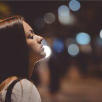 Junge schöne Frau, die sich in der Stadt in Seitenansicht auf eine Straßenlaterne stützt