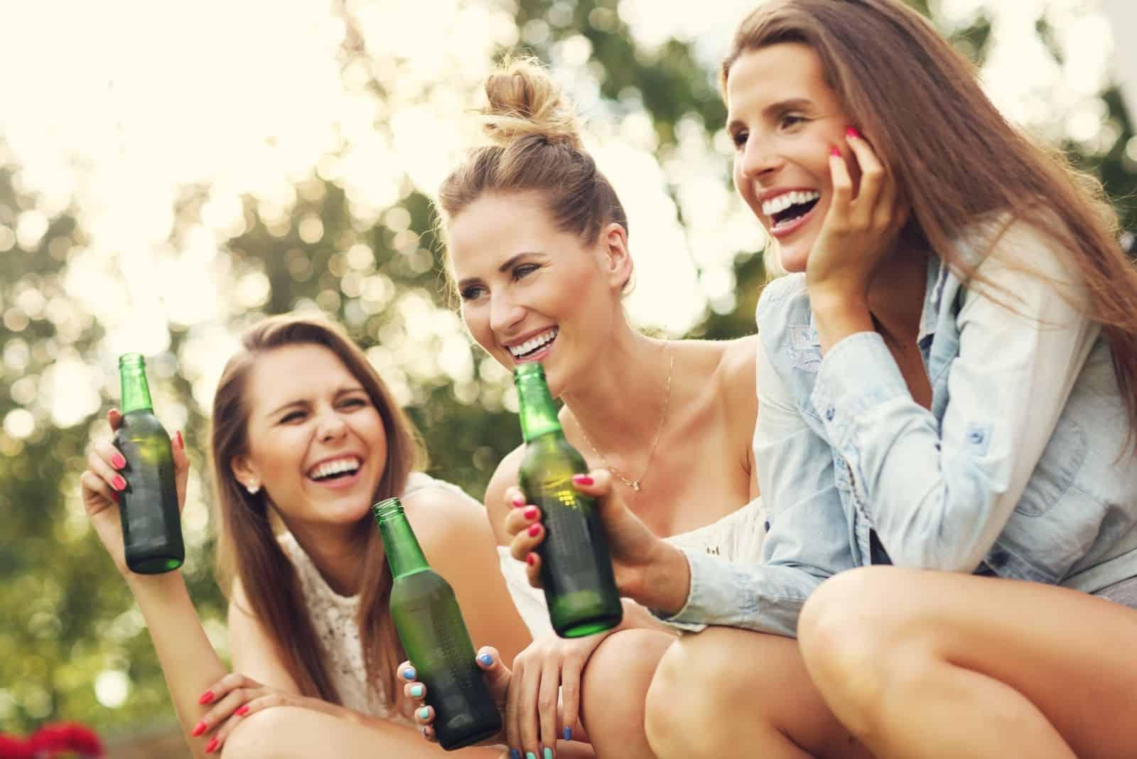 Bild, das glückliche Damen darstellt, die Damen trinken im Freien trinken