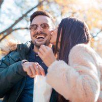 Romantisches Paar, das auf der Bank sitzt und schöne Momente des Glücks und der Freude im Herbstpark hat