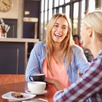 lächelnde Frauen sitzen und reden
