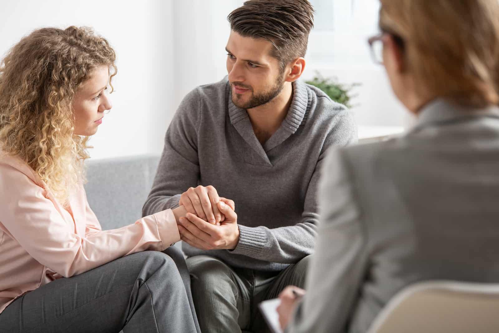 Ein Mann hält die Hand einer Frau, während er mit einem Psychiater spricht