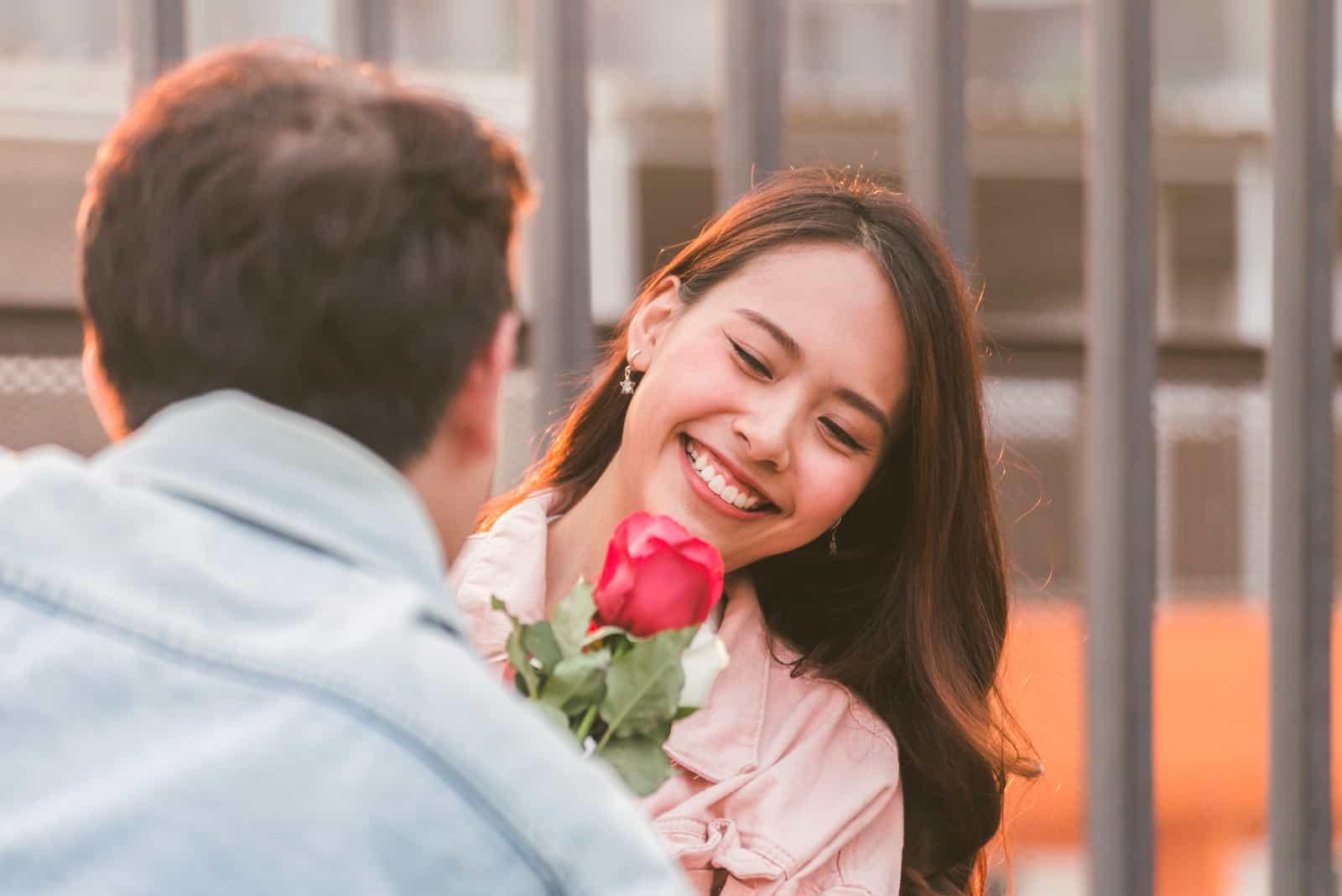 Ein Mann hat einer schönen Frau eine Rose geschenkt