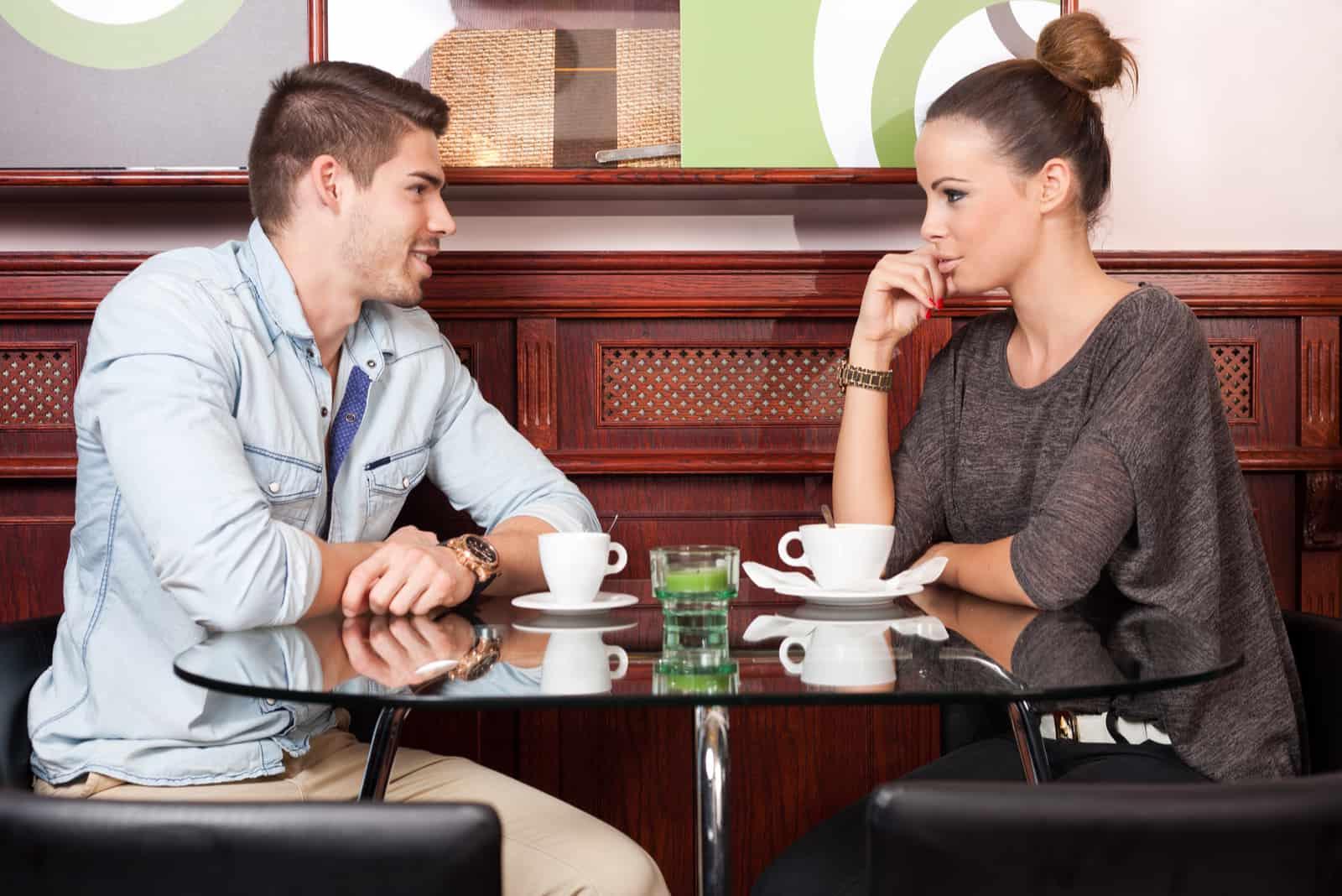 Ein Mann und eine Frau sitzen in einem Café an einem Tisch und unterhalten sich
