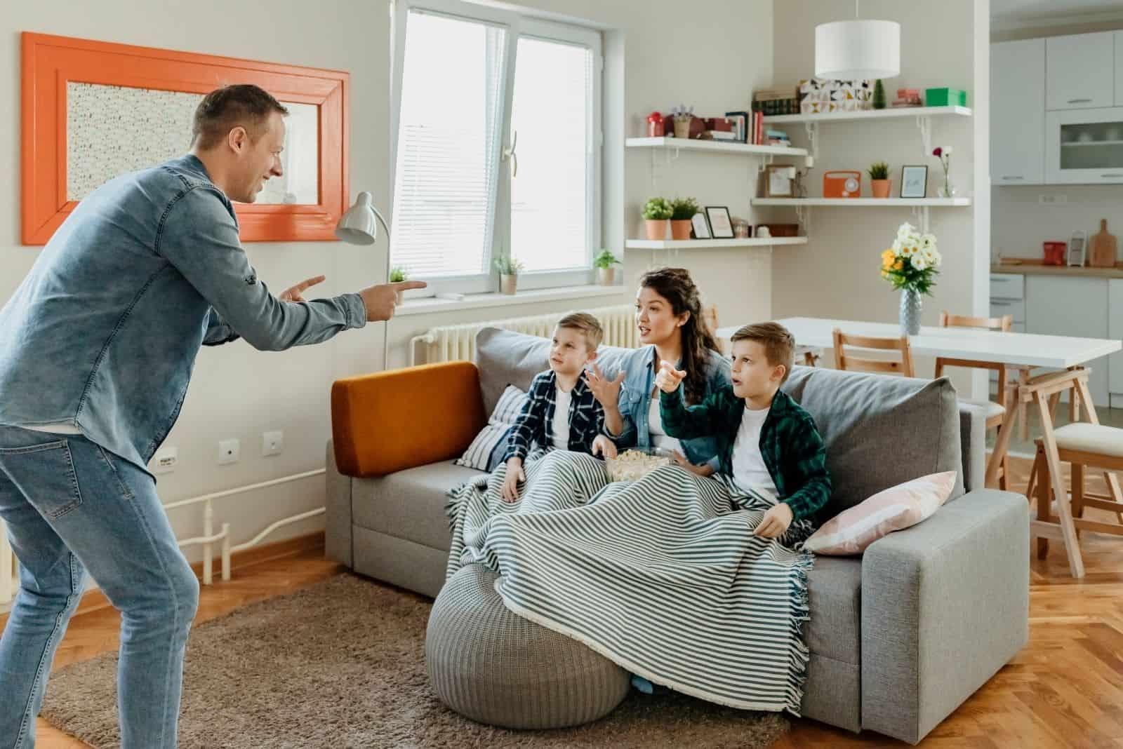 Familie spielt Ratespiel im Wohnzimmer mit dem Vater, der vor der Mutter und den Kindern steht