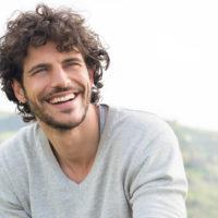 ein lächelnder Mann mit krausem Haar