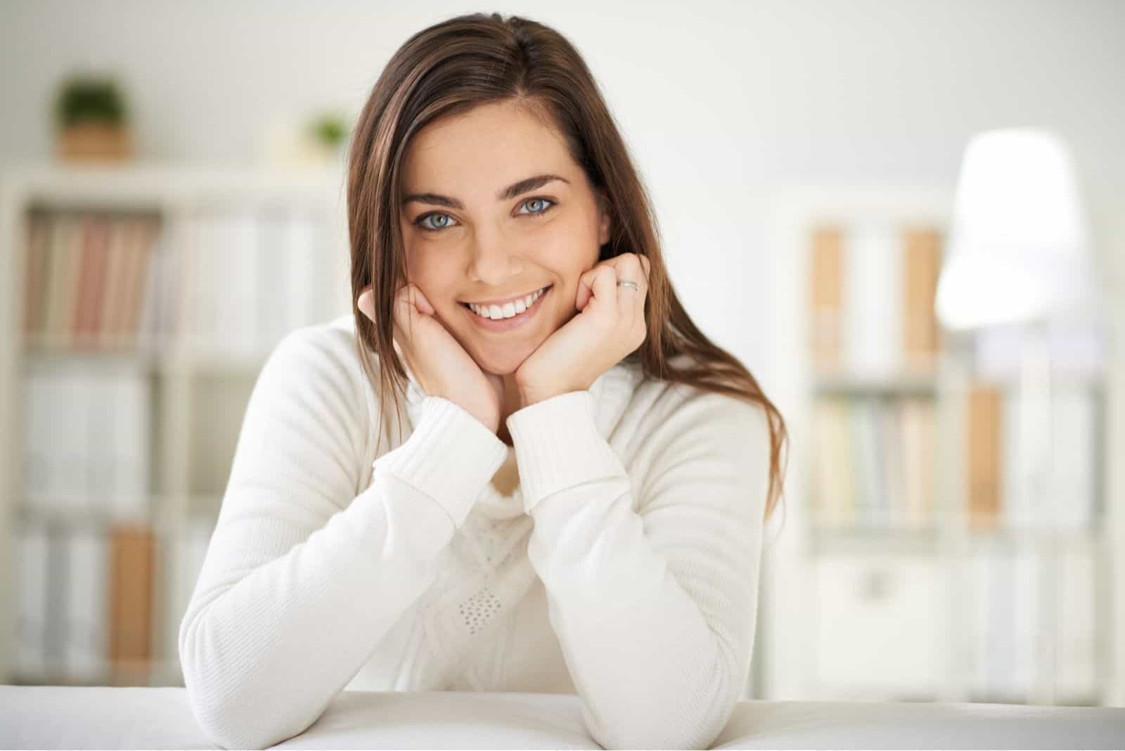 Frau in Weiß Pullover lächelnd in der Küche