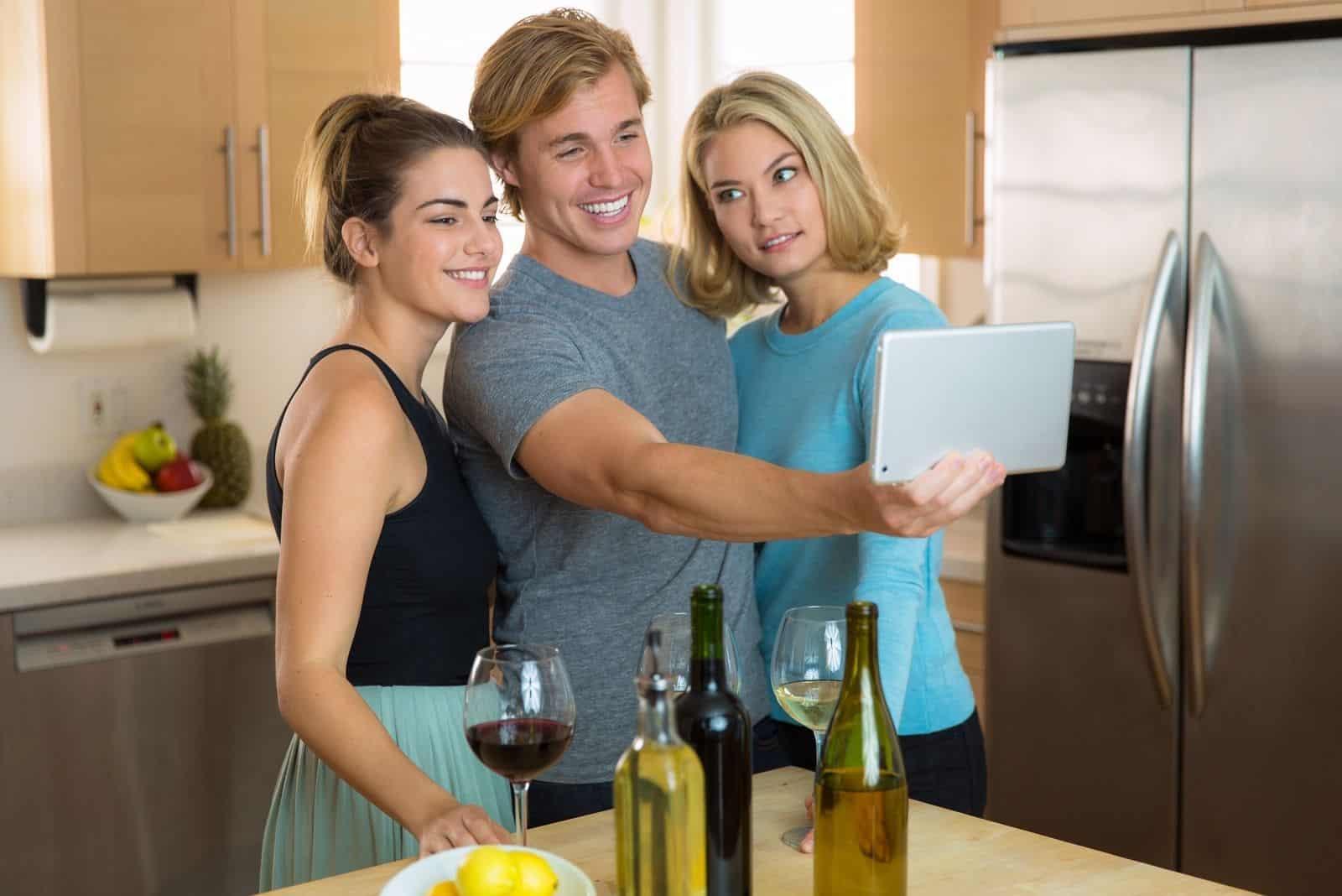 Frau ist eifersüchtig wie nah ihre Freundin ihrem Freund ist und ein Selfie macht