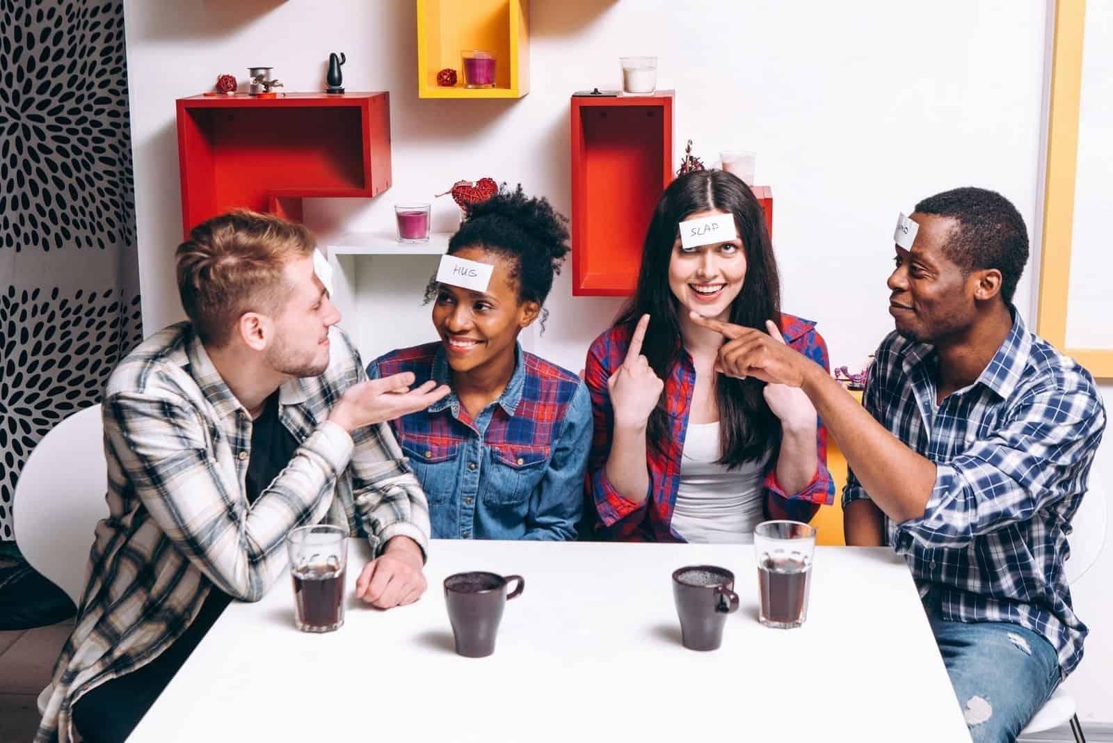 Freunde Ratespiel drinnen gespielt mit Kaffee auf dem Tisch