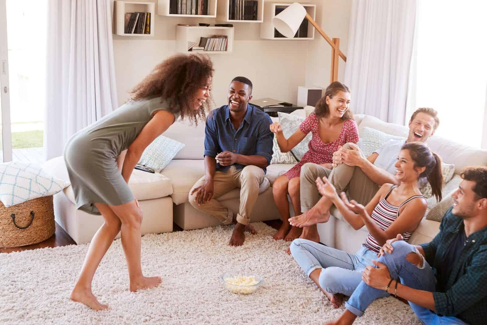 Freunde, die im Wohnzimmer Scharade spielen