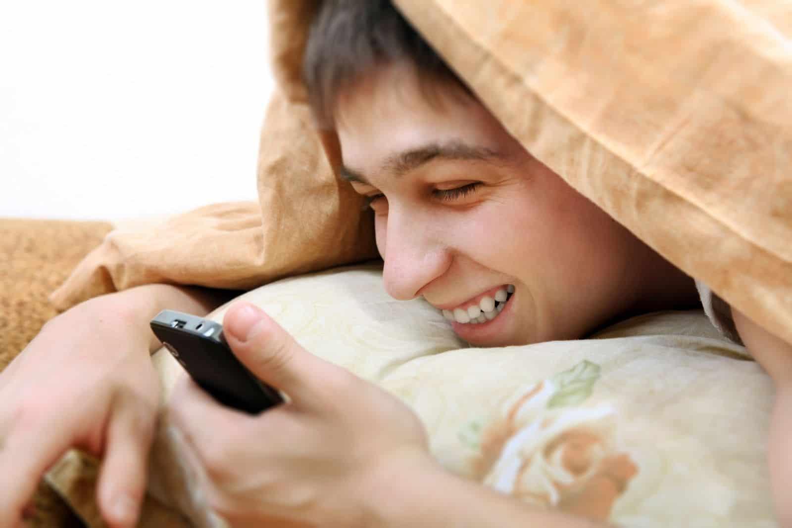 fröhlicher Teenager mit Handy bedeckt mit Decke auf dem Bett liegend