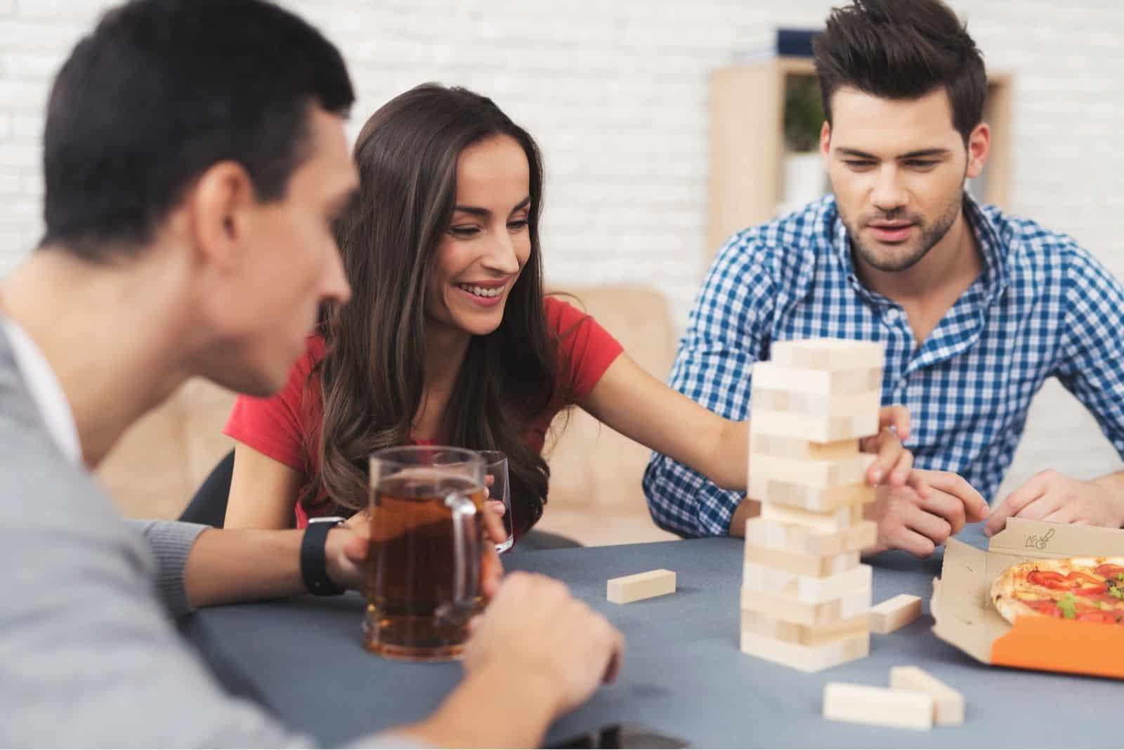 Gesellschaft von jungen Leuten Jenga-Spiel mit Bier und Pizza spielen