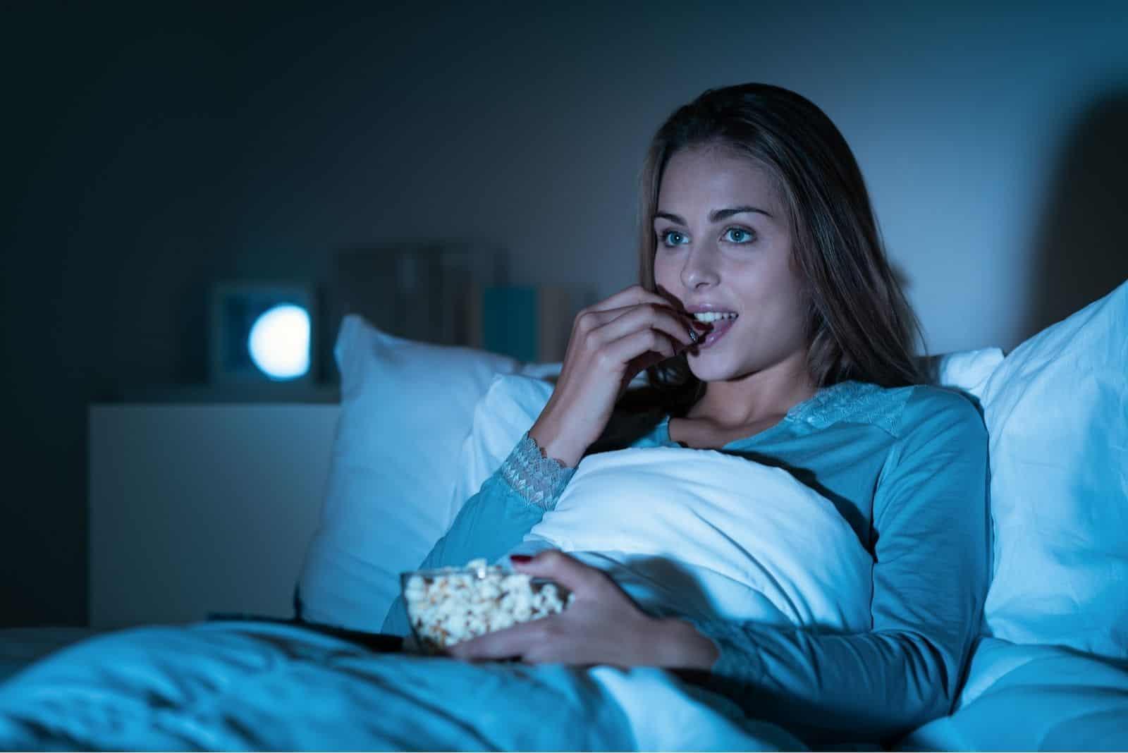 Glückliche Frau, die sich entspannt Nachts im Bett fernsehen und Popcorn essen