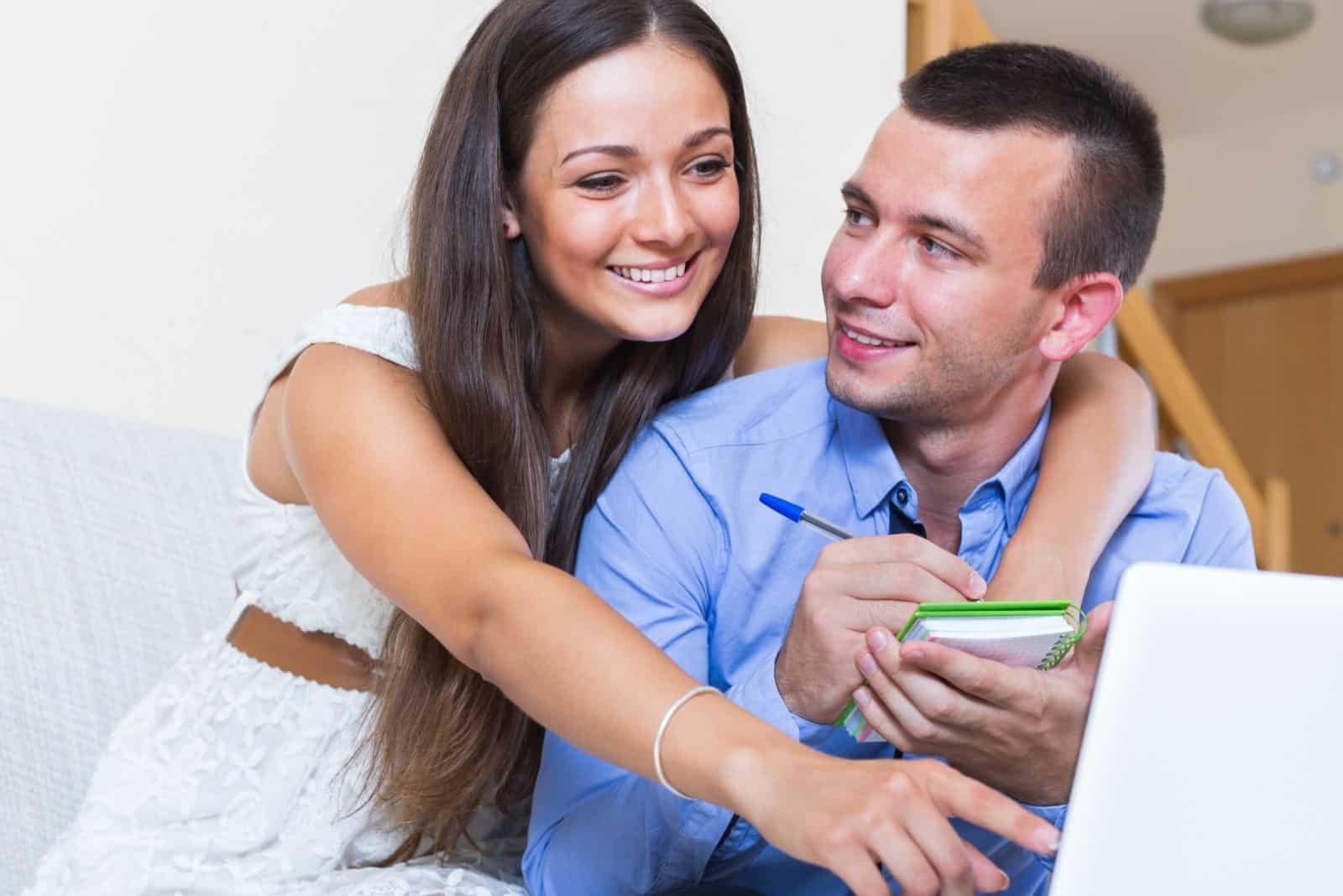 Glückliches Ehepaar Liste für den Online-Einkauf zu Hause erstellen