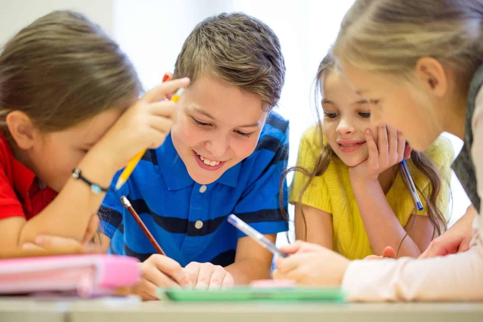 Grundschulkinder schreiben auf Papier teilen sich den gleichen Tisch