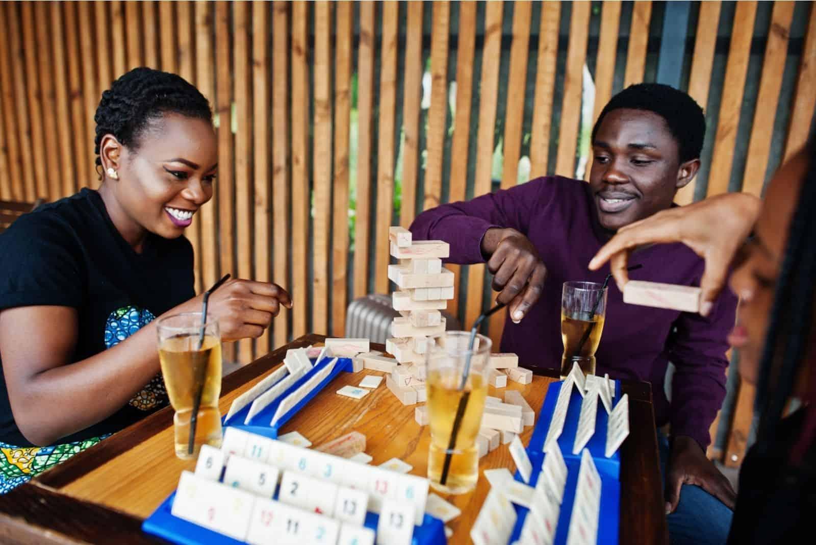 Gruppe afroamerikanischer Freunde trinken und spielen Jenga-Spiel