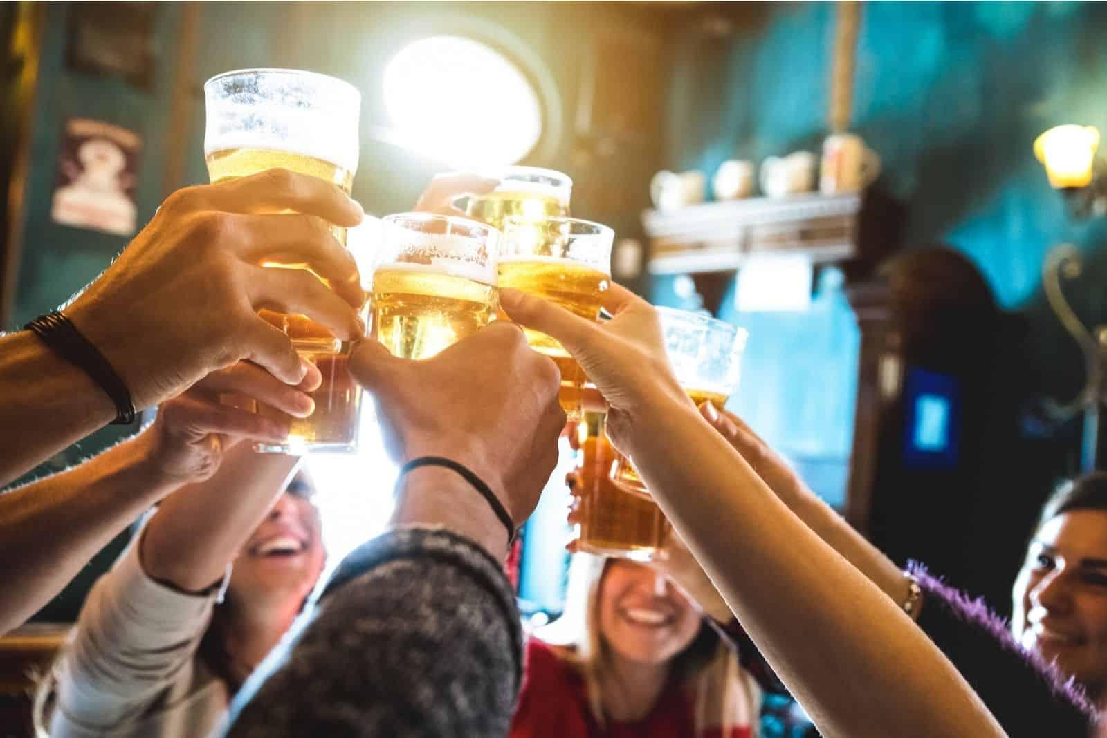Gruppe glücklicher Freunde Bier im Brauereirestaurant anstoßen