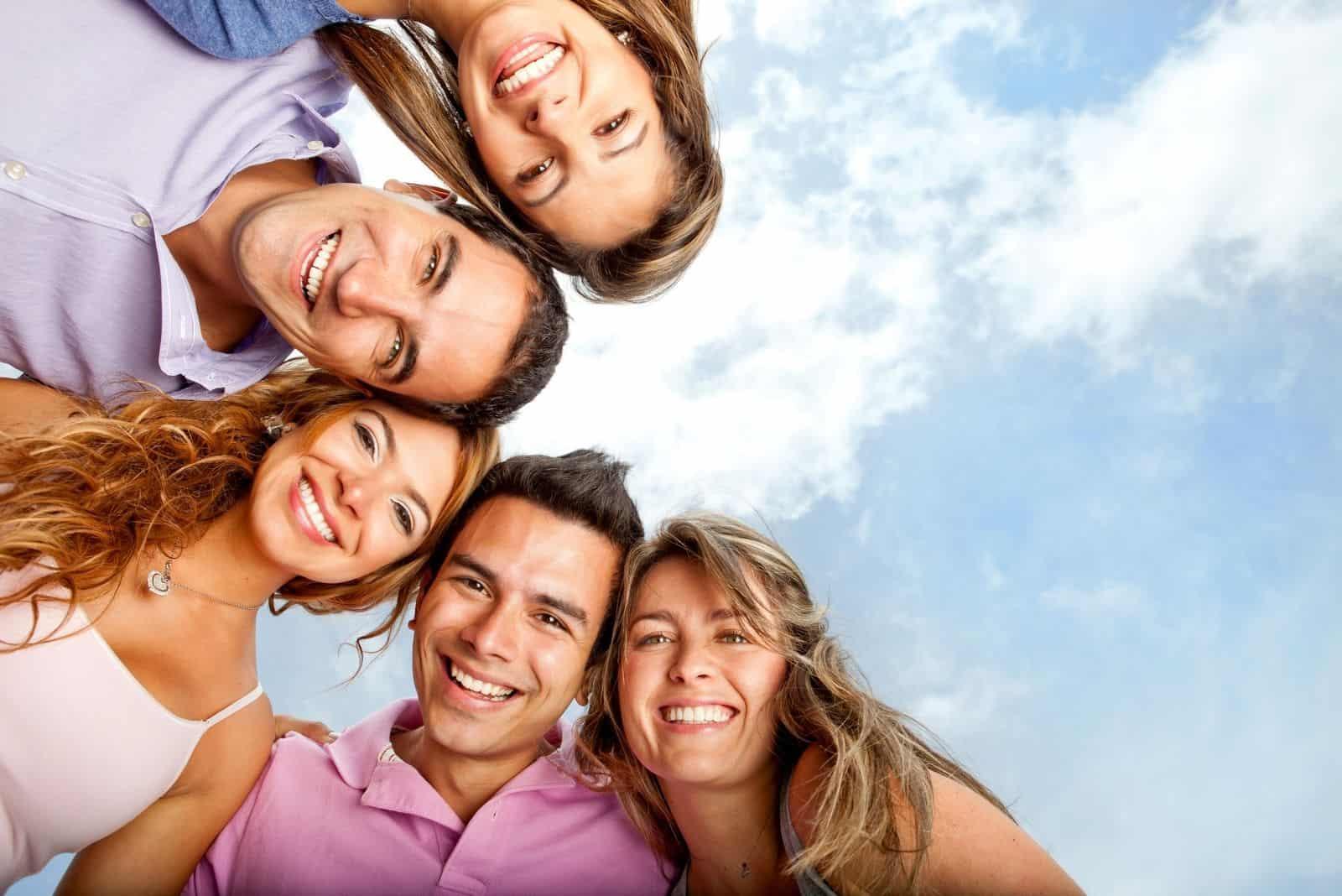 Gruppe glücklicher Menschen nebeneinander in niedrigem Winkel umgeben