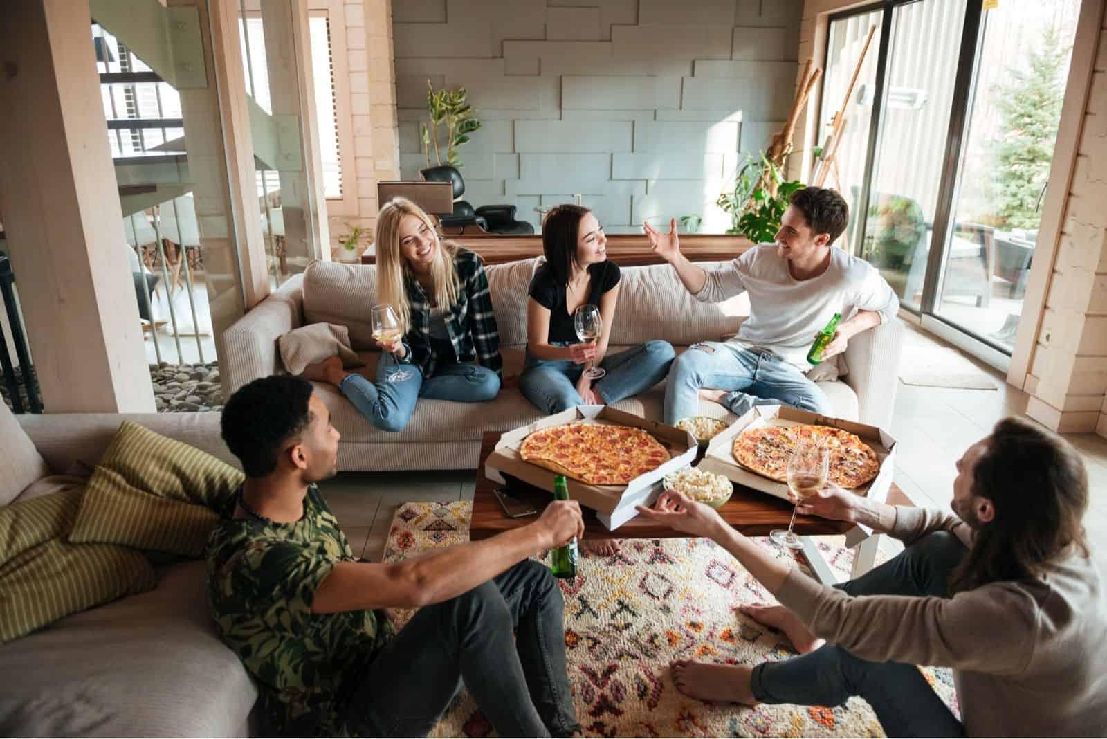 Gruppe junger fröhlicher Freunde eine gute Zeit beim Pizza- und Bieressen im Wohnzimmer haben