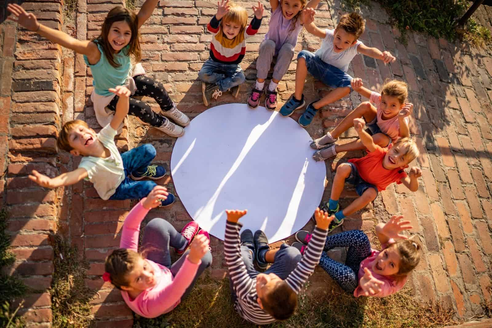 Gruppe von Kindern Kreisen um einen weißen Kreis in der Kopfansicht