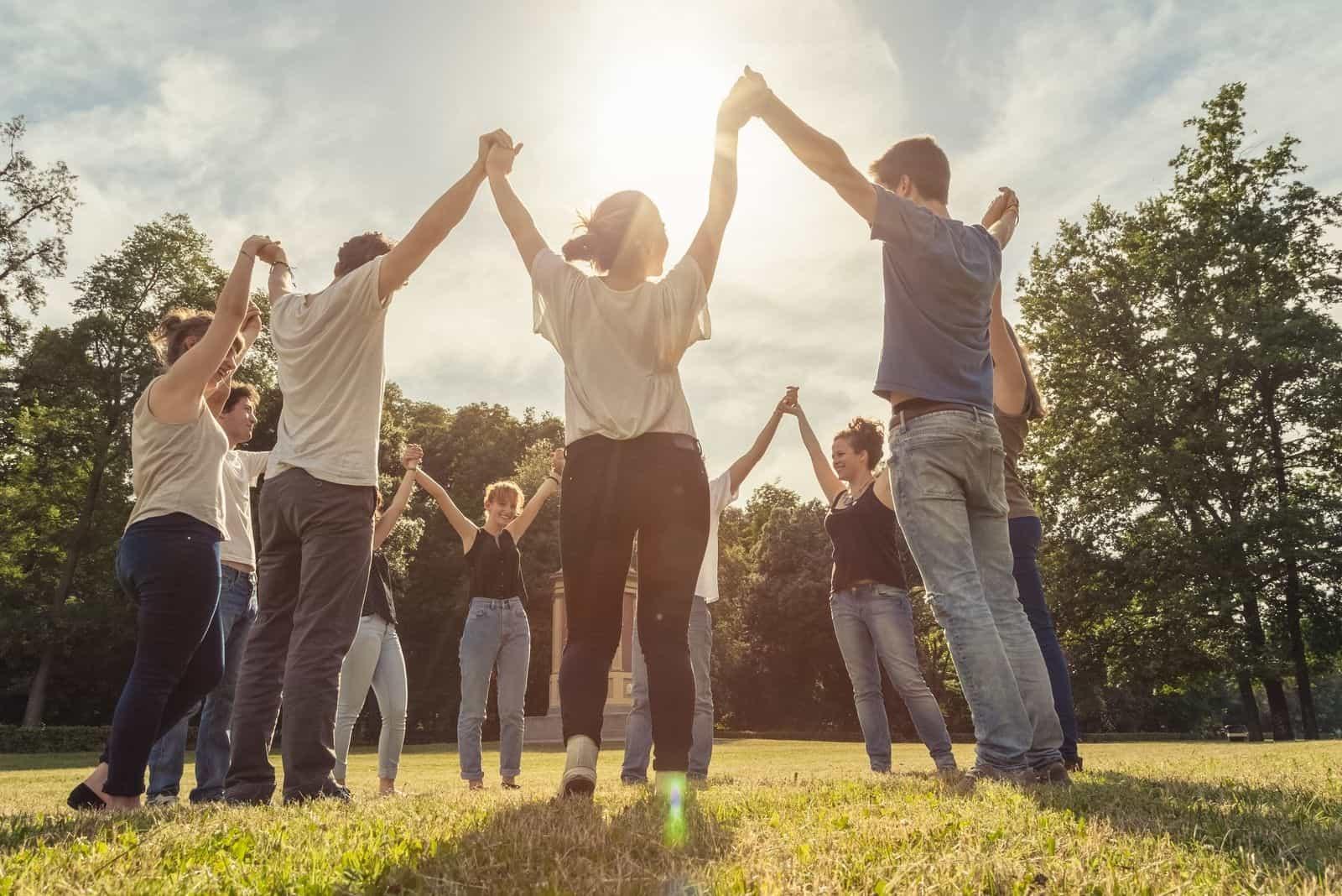 Gruppe von zehn Freunden, die Händchen halten, sie hochheben und herumkreisen und im Freien stehen