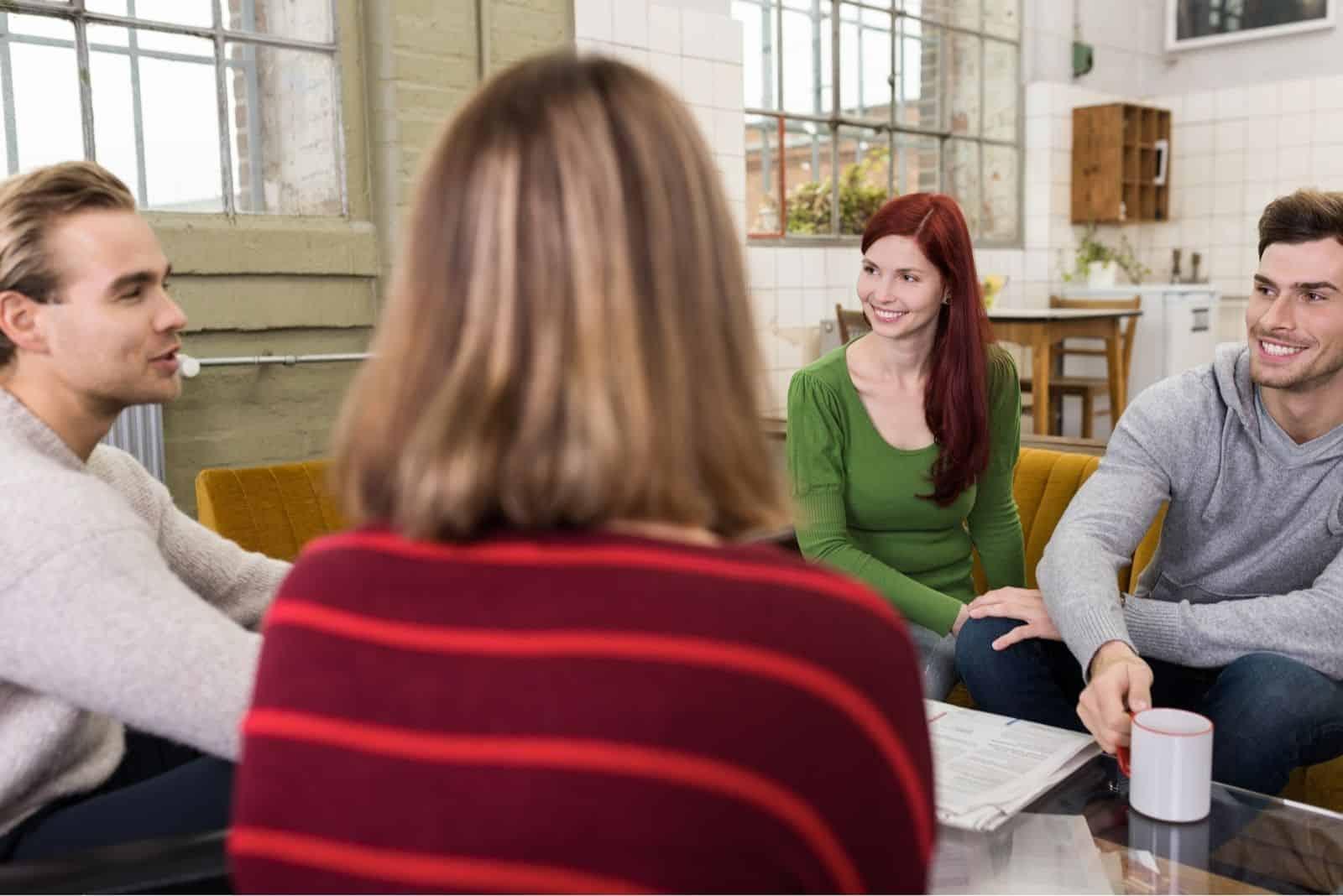 Gruppe weißer Freunde, die sich beim Kaffeetrinken im Kreis unterhalten