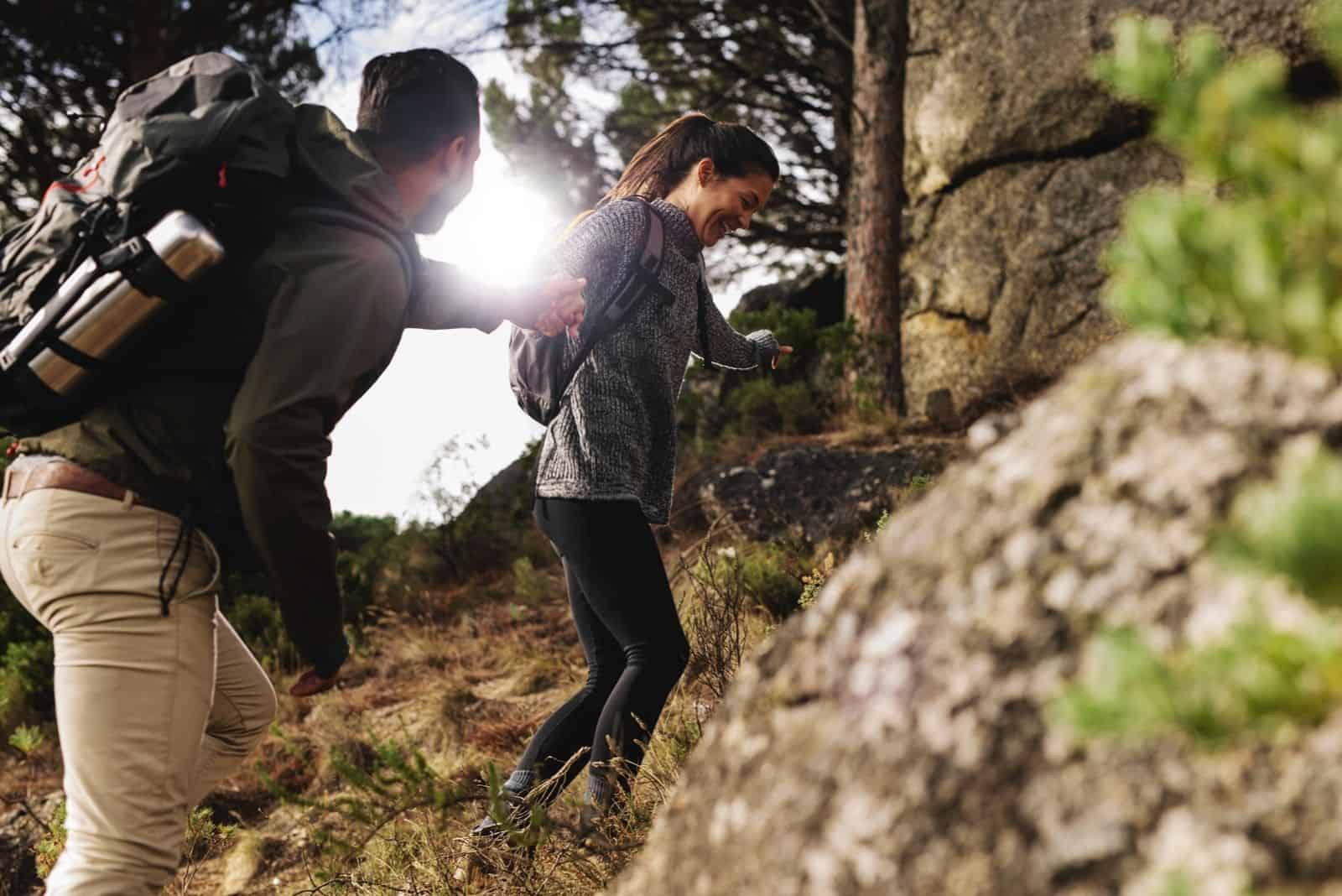 Junge Frau mit ihrem Freund wandern durch den bergweg