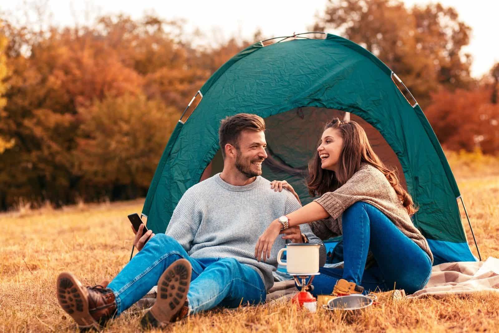 Junges Paar im Campingurlaub Sitzen und Lachen am Campingzelt