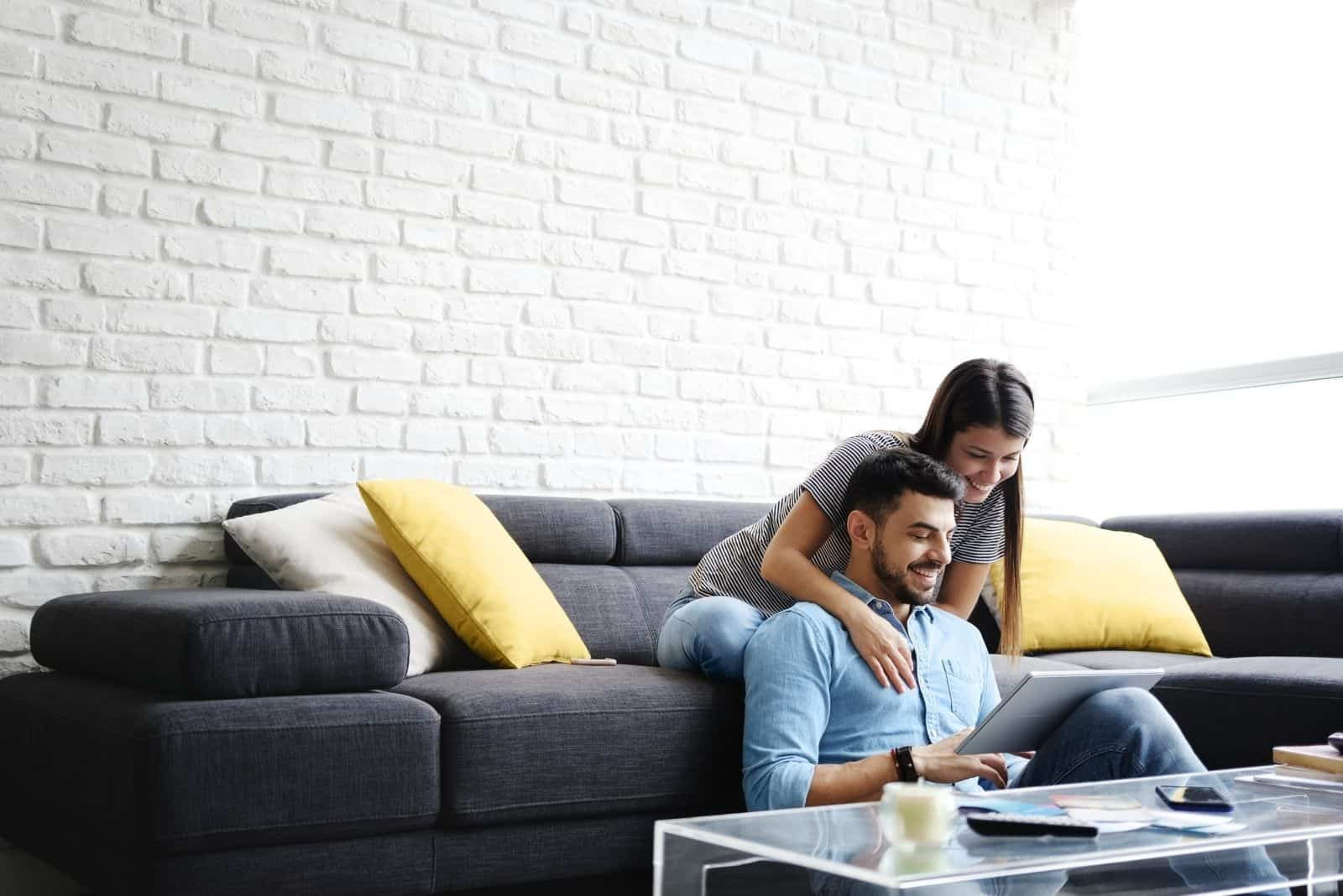 Junges hispanisches Paar zu Hause auf der Couch sitzen und einen Tablet-PC für Internet und Social Media nutzen