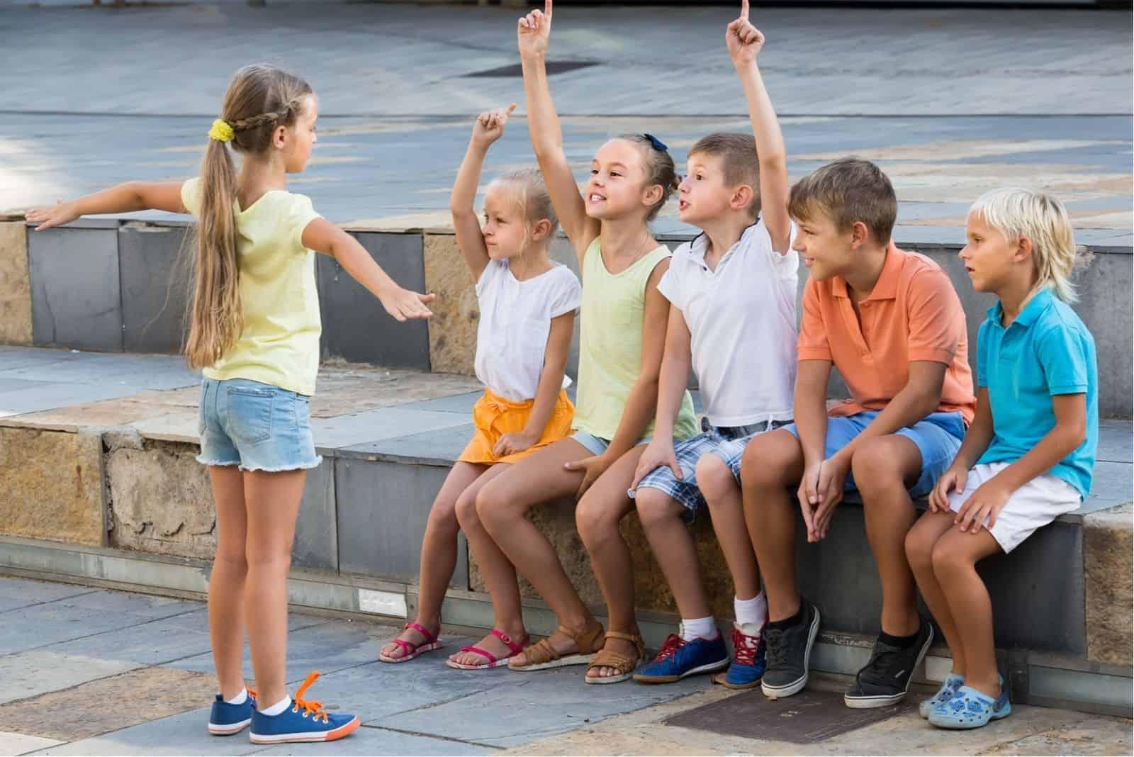 Kinder im Schulalter Spielen im Freien mit einem Lautsprecher vor fünf Kindern